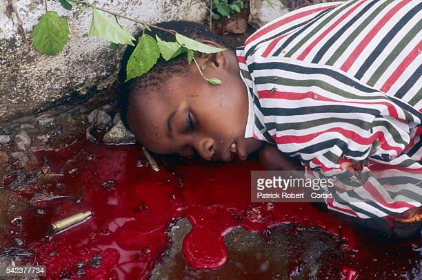 A refugee child killed by soldiers from the government's 72nd Battalion lies in a pool of blood alongside a street in Congo Town Responding to years...