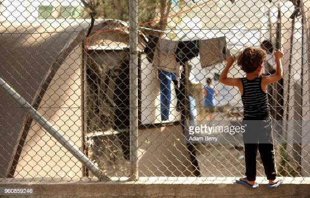 A refugee child looks through a fence at the Moria refugee camp on May 20 2018 in Mytilene Greece Despite being built to hold only 2500 people the...