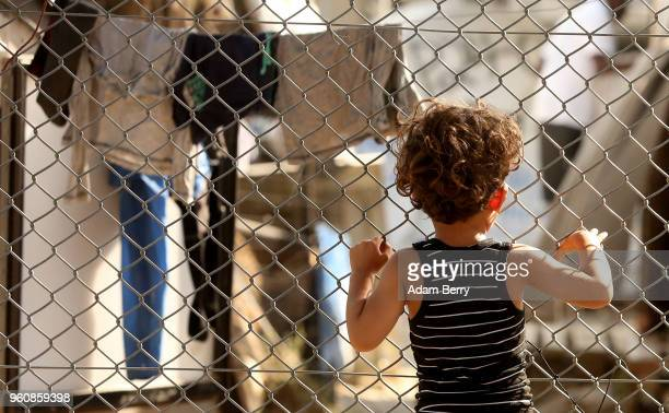 Refugee child looks through a fence at the Moria refugee camp on May 20, 2018 in Mytilene, Greece. Despite being built to hold only 2,500 people, the...