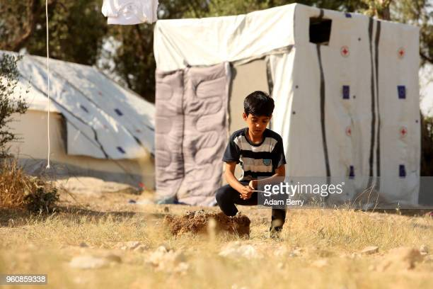 A refugee child plays alone at the Moria refugee camp on May 20 2018 in Mytilene Greece Despite being built to hold only 2500 people the camp on the...