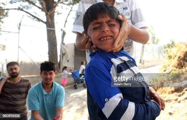 A refugee child plays with another at the Moria refugee camp on May 20 2018 in Mytilene Greece Despite being built to hold only 2500 people the camp...