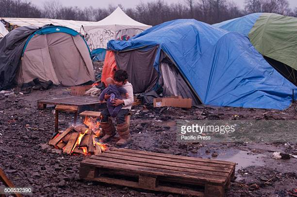 A refugee child plays with her doll by a camp fire in the refugee camp in Dunkirk where more than 3000 refugees live in dire conditions