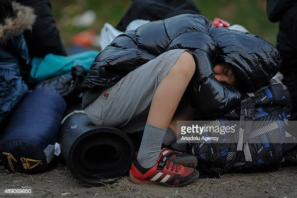 A refugee child sleeps on the bags at a makeshift camp in Tovarnik Croatia on September 19 2015 Refugees are crossing into Croatia from Serbia after...