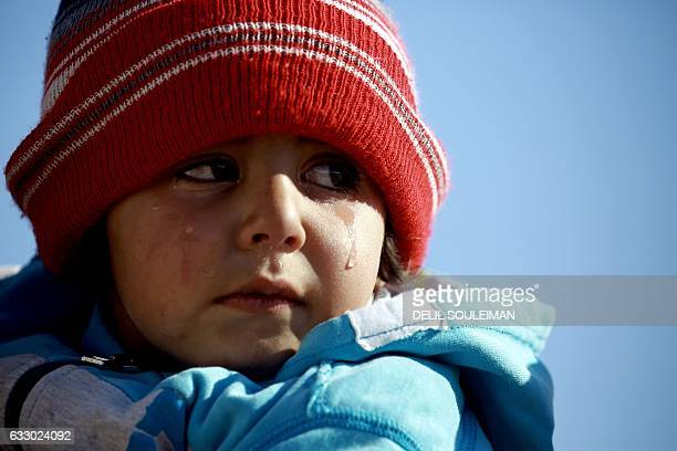 A refugee child who fled the Iraqi city of Mosul due to the fighting between government forces and Islamic State group jihadists cries at the UNrun...