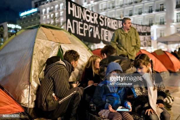 Refugee childen play with a mobile phone by their tents at the Athens central Syntagma square opposite of the Greek parliament as refugee families...