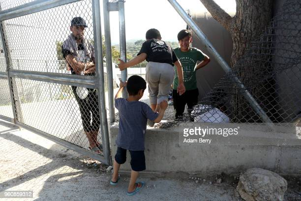 Refugee children climb through a fence at the Moria refugee camp on May 20 2018 in Mytilene Greece Despite being built to hold only 2500 people the...