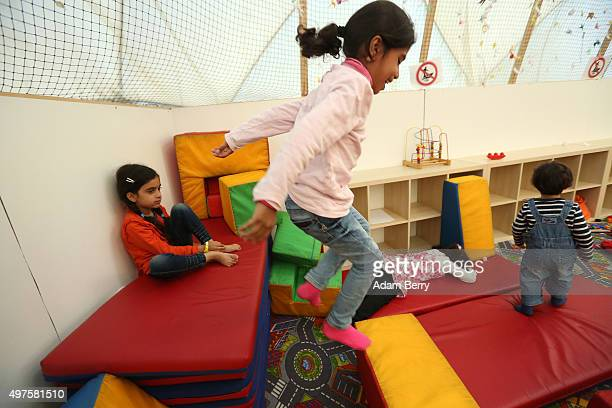 Refugee children from Iraq and Syria play in the children's area of an airdome used as a temporary shelter for refugees on September 26 2015 in...