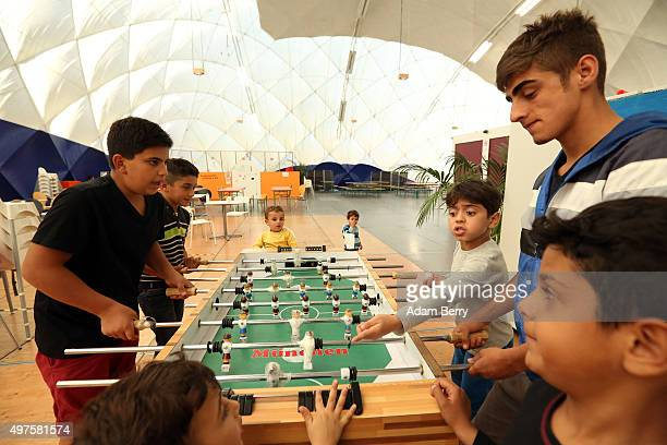 Refugee children from Iraq play Foosball in an airdome used as a temporary shelter for refugees on September 26 2015 in Berlin Germany Following the...