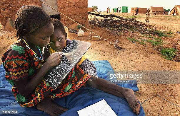 Refugee children from the Darfur region of Sudan practice arabic arithmetic outside their tent in the Kounoungo refugee camp September 1 2004 in Chad...
