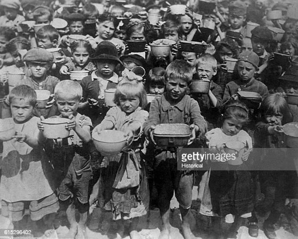 Refugee children in Poland hold up bowls for food during World War I