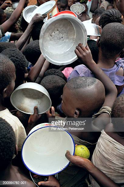 Refugee children (4-11) standing in queue,holding bowls,elevated view