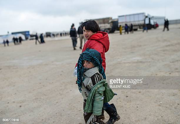 Refugee children walk in a camp near the Turkish border crossing as Syrians fleeing the northern embattled city of Aleppo wait on February 6 2016 in...