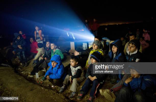 Refugee children watch a film outside in the refugee camp at the Greek-Macedonian border in Idomeni, Greece, 05 March 2015. Only a few refugees...
