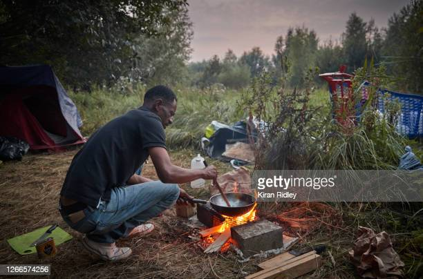 Refugee cooks on a small fire in a makeshift camp in wasteland on the outskirts of Calais after recent evictions by police at previously established...