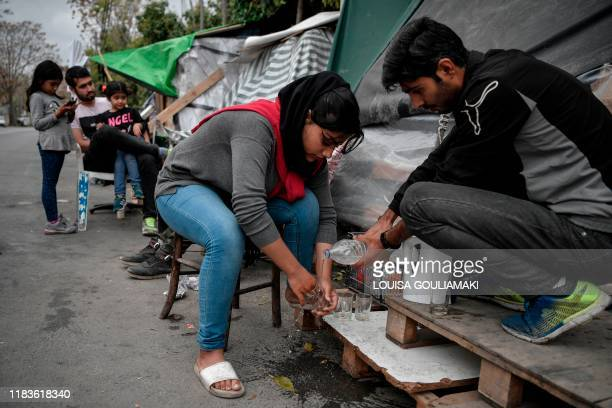 A refugee couple wash glasses to prepare tea next to their tents set up on a street outside Eleonas refugee camp in Athens on November 20 2019 Some...