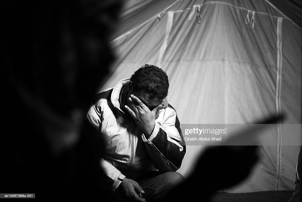 A Refugee cries as he and his friends sit in their tent, February 4, 2007, in a camp in the no-mans land between the Syrian and Iraqi borders. The Camp houses Iraqi and Palestinian refugees who fled violence in Iraq but are not allowed into Syria. Sectarian violence and civil war in Iraq are pushing more and more Iraqis to seek refuge in neighboring counties where more than 2 million Iraqis have settled according to the UNHCR. The biggest refugee crisis in the Middle East since The creation of Israel in 1948.