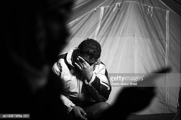 A Refugee cries as he and his friends sit in their tent February 4 in a camp in the nomans land between the Syrian and Iraqi borders The Camp houses...