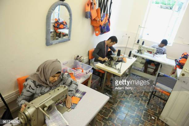 Refugee employees sew life preserver material and fabric together to make bags for sale at the Lesvos Solidarity organization's Safe Passage Bags...
