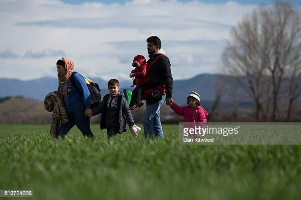 Refugee families walk through fields towards the the GreekMacedonia border on March 04 2016 in Idomeni Greece The transit camp at the border is...