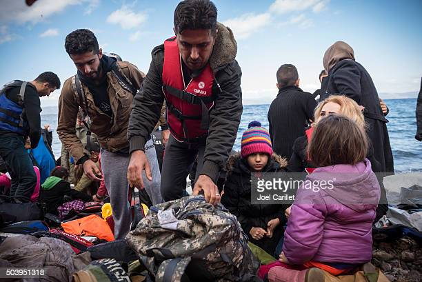refugee family arriving on lesbos, greece - human trafficking stock photos and pictures