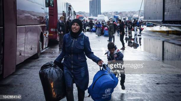 A refugee family carry its belonging items following disembark at the Port of Piraeus 29 September 2018 Thousand migrants and refugees are scheduled...