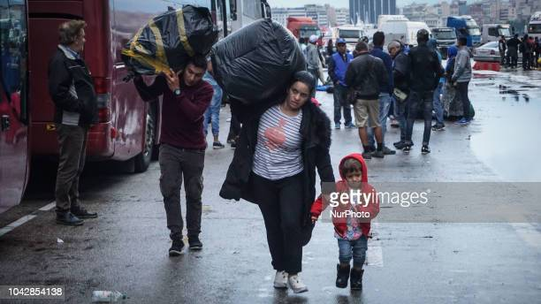 A refugee family carry its belonging items towards a coach bus as they disembark at the Port Piraeus 29 September 2018 Thousand migrants and refugees...