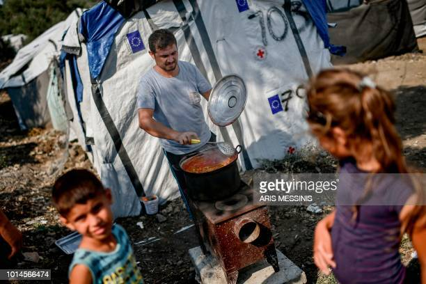 A refugee family from Syria prepare their lunch at a camp outside the Moria refugee camp in the island of Lesbos on August 5 2018