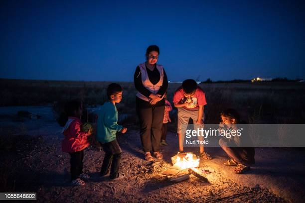 Refugee family in front of fire warming themselves A group of refugees outside in the field near Diavata refugee camp in Thessaloniki Greece on 26...