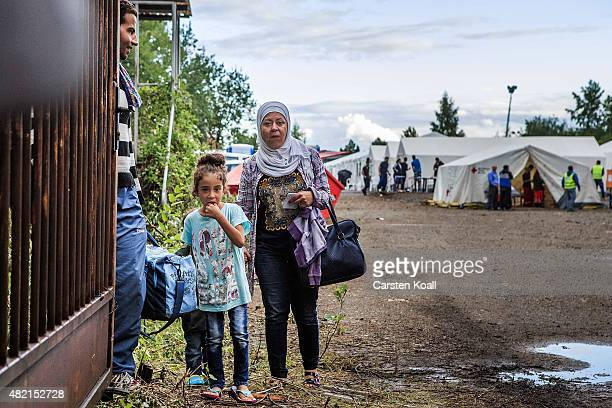 A refugee family waits on a gate inside a temporary tent camp on July 27 2015 in Dresden GermanyThe German Red Cross set up the camp last week and...