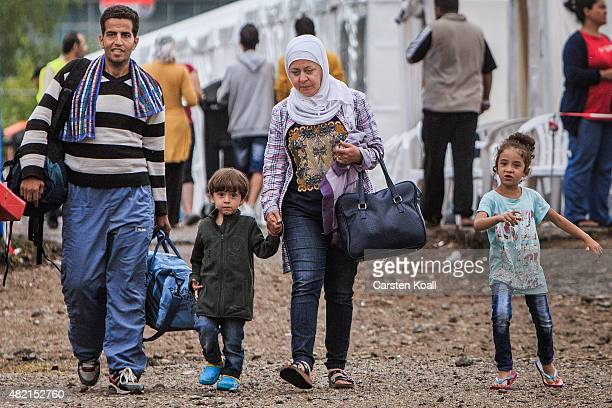 A refugee family walk inside a temporary tent camp on July 27 2015 in Dresden GermanyThe German Red Cross set up the camp last week and plan to house...