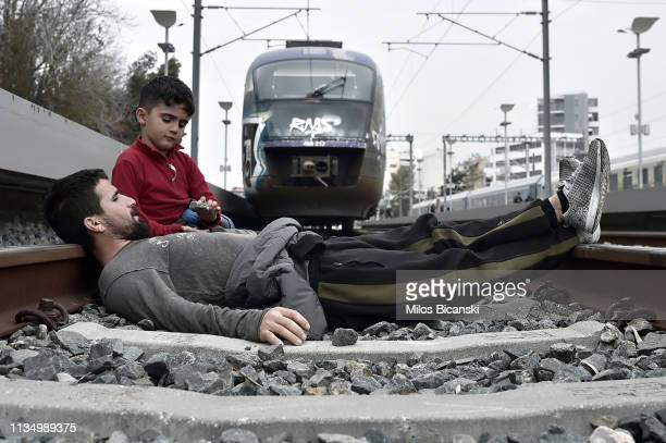 A refugee father and son lie on railway tracks to prevent a train from leaving a station during a protest on April 5 2019 in Athens Greece Dozens of...