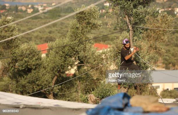 A refugee fixes a broken electricity cable at the Moria refugee camp on May 20 2018 in Mytilene Greece Despite being built to hold only 2500 people...