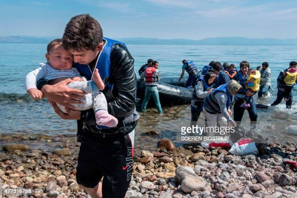A refugee from Afghanistan carries a baby on arrival on the shores of Lesbos near Skala Skamnias Greece on June 2 2015 Lesbos the Greek vacation...