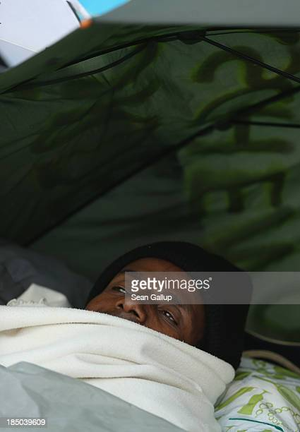 A refugee from Ethiopia lies under an umbrella against the rain on the 8th day of a hunger strike in front of the Brandenburg Gate on October 17 2013...