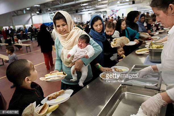 Refugee from Kabul in Afghanistan Nafise Rabani holds 21day old baby Nina Asis and Mina Berlatia holds baby Arshan while taking food during the 139th...