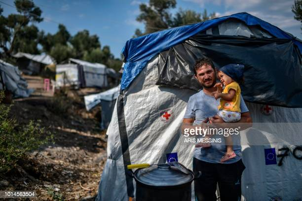 A refugee from Syria holds his child outside a tent at a camp next to the Moria refugee camp in the island of Lesbos on August 05 2018