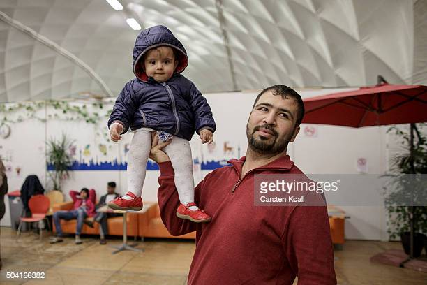 A refugee from Syria holds his daughter on his hand at a shelter for migrants and refugees run by the Berliner Stadtmission charity on January 9 2016...
