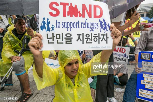 A refugee from Yemen holds a sign pleading for support for refugees on September 16 2018 in Seoul South Korea Activists gathered to protest for and...