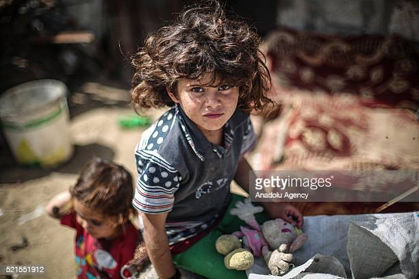 A refugee girl holding her toy looks on at Khan Yunis refugee camp in Khan Yunis Gaza on April 16 2016 Khan Yunis Camp was established after the 1948...