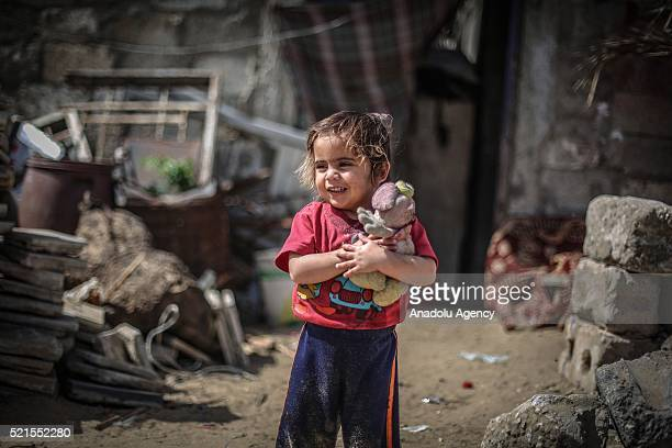 Refugee girl holding her toy looks on at Khan Yunis refugee camp, in Khan Yunis, Gaza on April 16, 2016. Khan Yunis Camp was established after the...