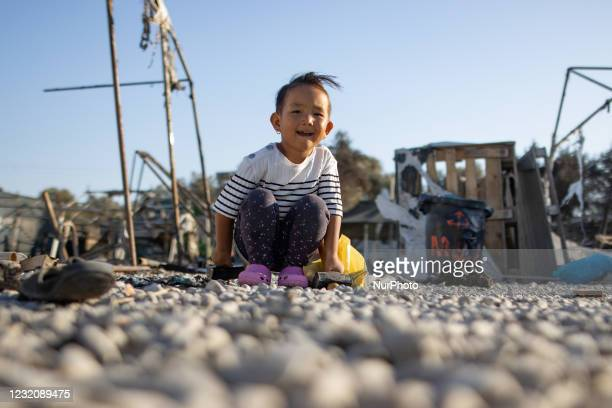 Refugee girl playing in the ashes of the ruined from the fire camp. Close up of underaged, minors asylum seekers who live with their families around...