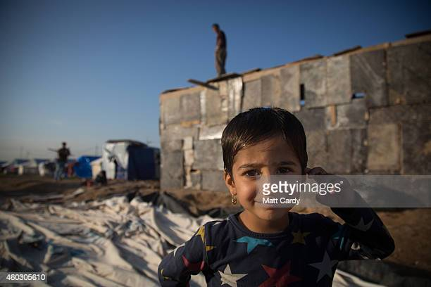 Refugee girl, who was forced to flee her home as the Islamic State advanced earlier this year, stands in front of a shelter being built at the...