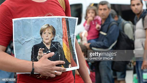 Refugee holds a picture of German Chancellor Angela Merkel after the arrival of refugees at the main train station in Munich, southern Germany,...