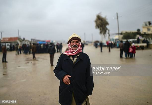 A refugee is pictured near the Turkish border crossing gate as Syrians fleeing the northern embattled city of Aleppo wait on February 6 2016 in Bab...