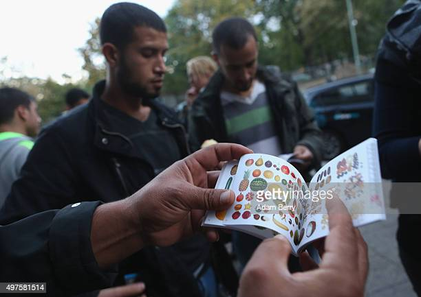 A refugee looks at a book full of pictures to be used to communicate nonverbally with locals as he waits outside the LaGeSo State Office for Health...