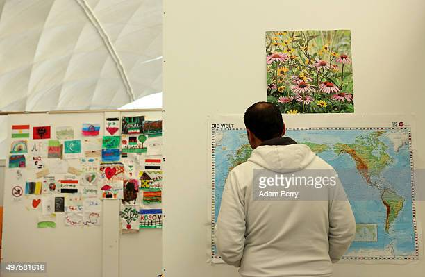 A refugee looks at a map of the world in an airdome used as a temporary shelter for refugees on September 26 2015 in Berlin Germany Following the...