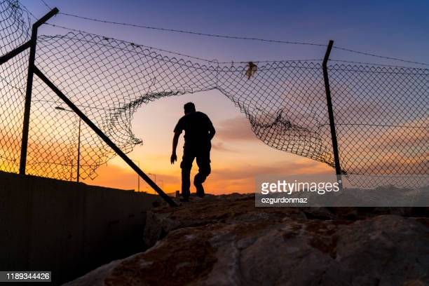 refugee man running behind fence, - syria stock pictures, royalty-free photos & images