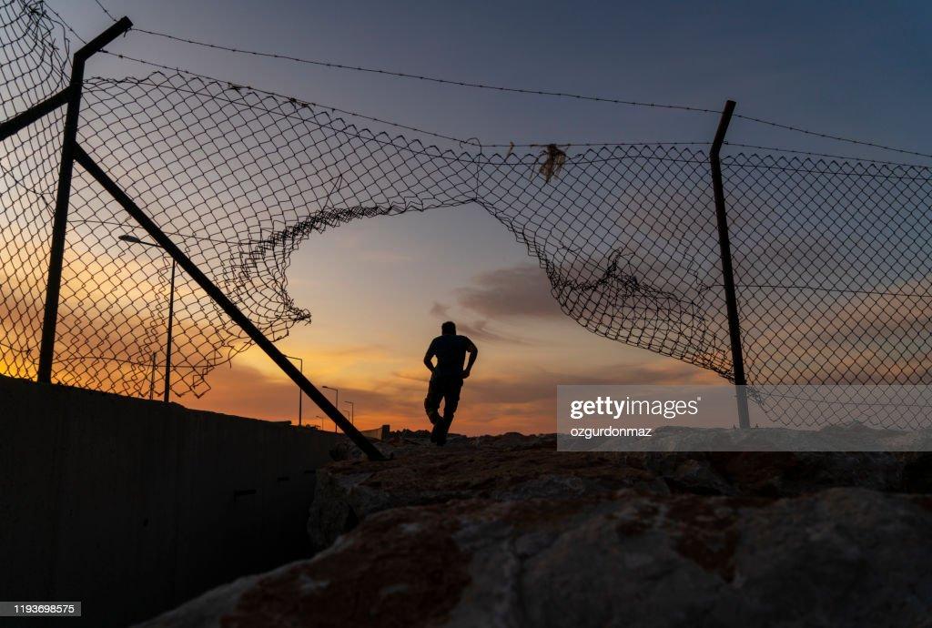 フェンスの後ろを走る難民の男、 : ストックフォト