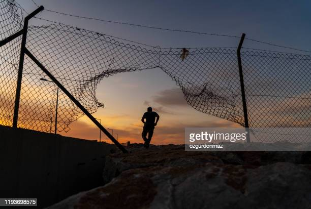 refugee man running behind fence, - escaping stock pictures, royalty-free photos & images