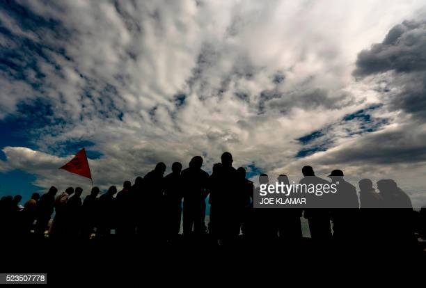 Refugee men attend a silent protest at a makeshift camp for migrants and refugees at the GreekMacedonian border near the village of Idomeni on April...